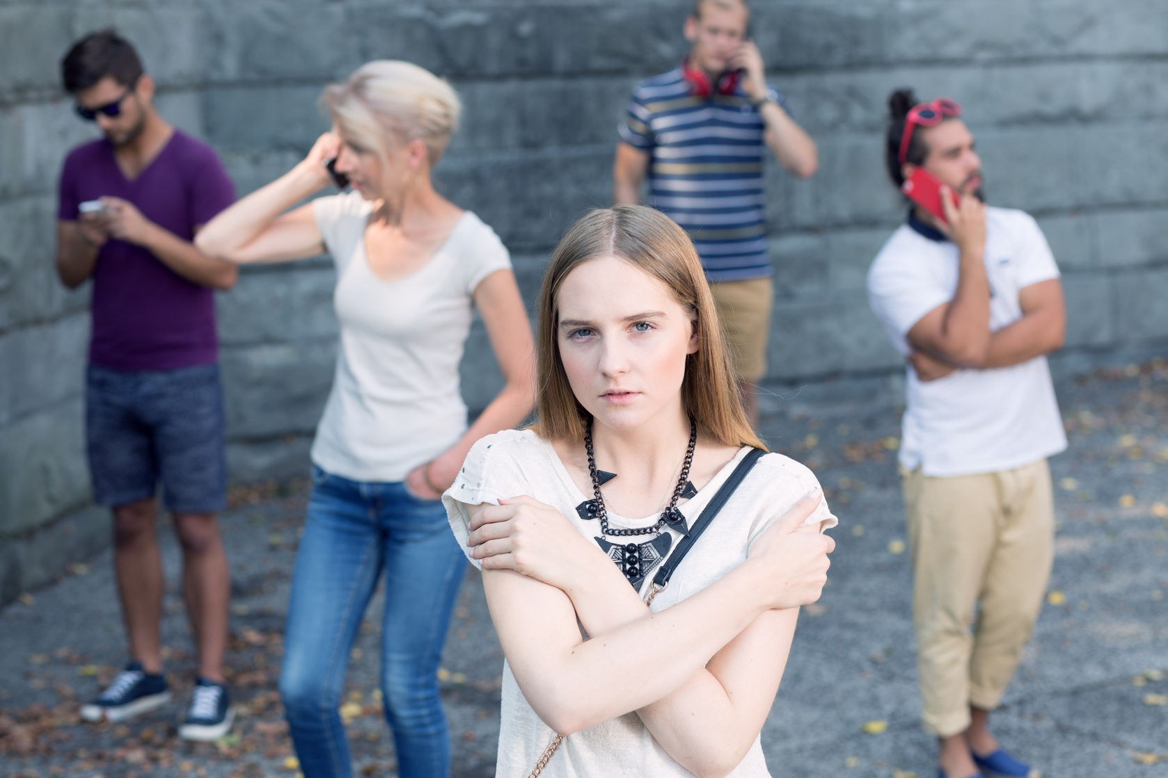 70228729 – pretty young girl lonely among people busy with mobile phones